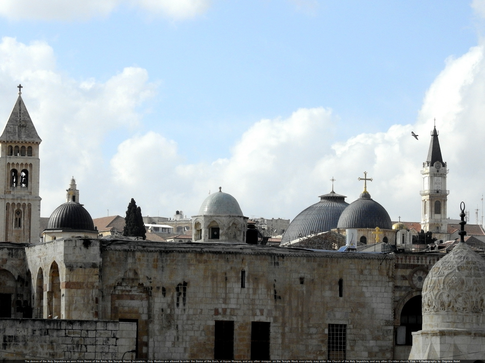 The domes of the Holy Sepulchre (note the Cross over the Catholicon; the Cross of Golgotha - symbol of the efforts of unity in the community of Christian faith) as seen from Dome of the Rock, the Temple Mount, Jerusalem.  Only Muslims are allowed to enter the Dome of the Rock, al Aqusa Mosque, and any other mosque  on the Temple Mout; everybody may enter the Church of the Holy Sepulchre, and any other Christian church. Fine Art Photography by Zbigniew Halat