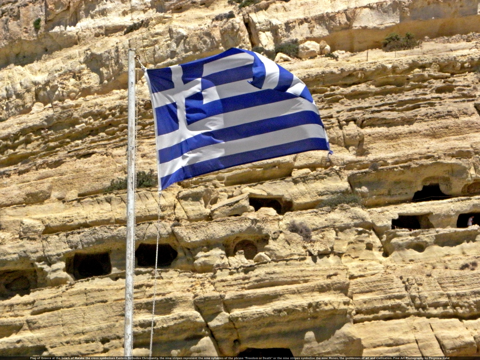 "Flag of Greece at the beach of Matala: the cross symbolises Eastern Orthodox Christianity, the nine stripes represent the nine syllables of the phrase ""Ελευθερία ή Θάνατος"" (""Freedom or Death"") or the nine stripes symbolise the nine Muses, the goddesses of art and civilisation. Fine Art Photography by Zbigniew Halat"